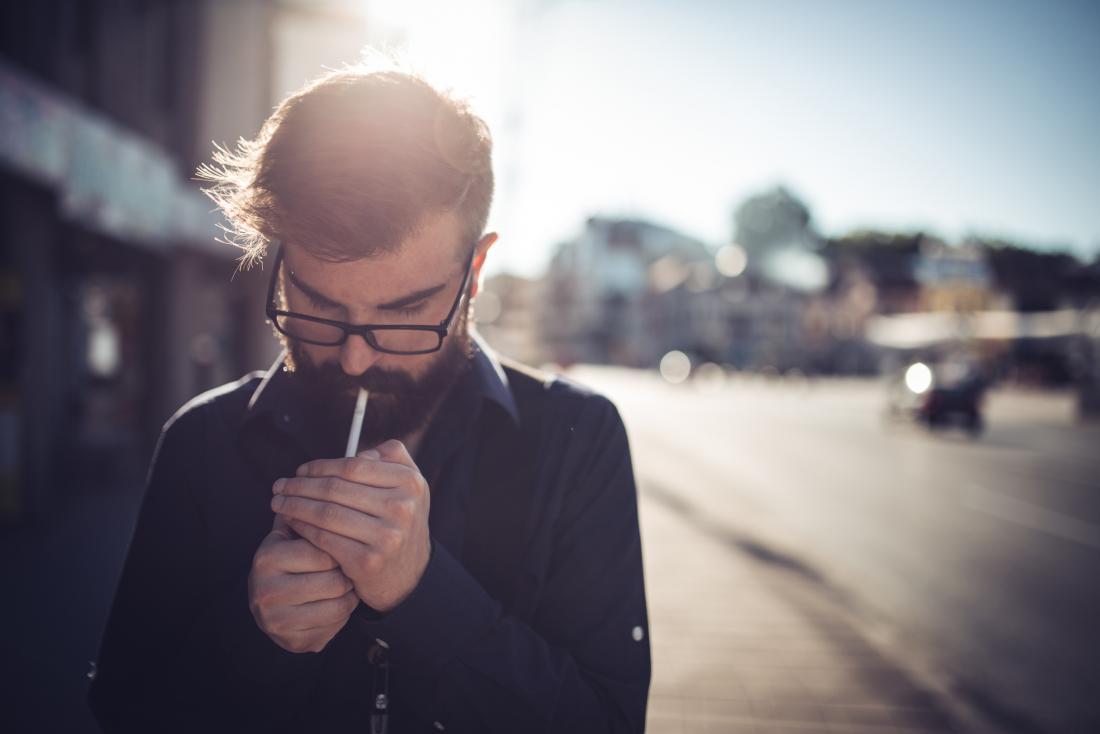 man lighting up his cigarette