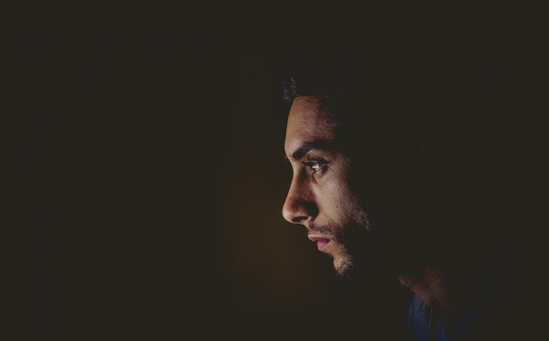 profile of sad man on dark background