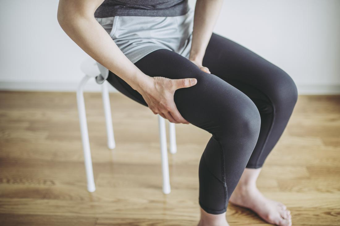 Person holding their thigh in pain due to muscle twitches while sitting on chair