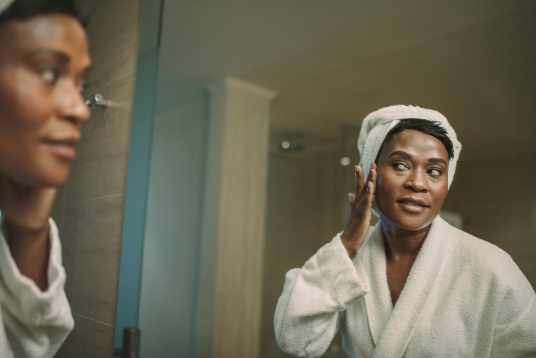 Woman in front of bathroom mirror applying CBD oil or moisturizer to her face to treat acne