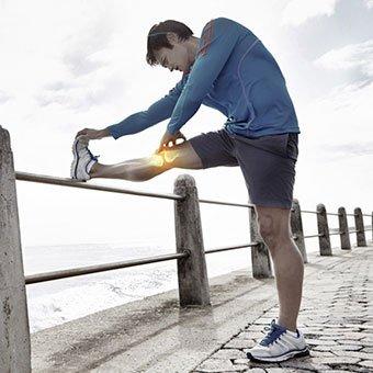 A runner stretches an injured knee.