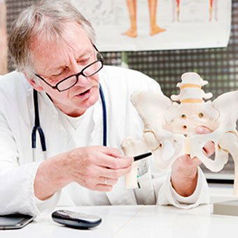 A doctor discusses a cortisone injection of the hip and possible side effects using an anatomic model.