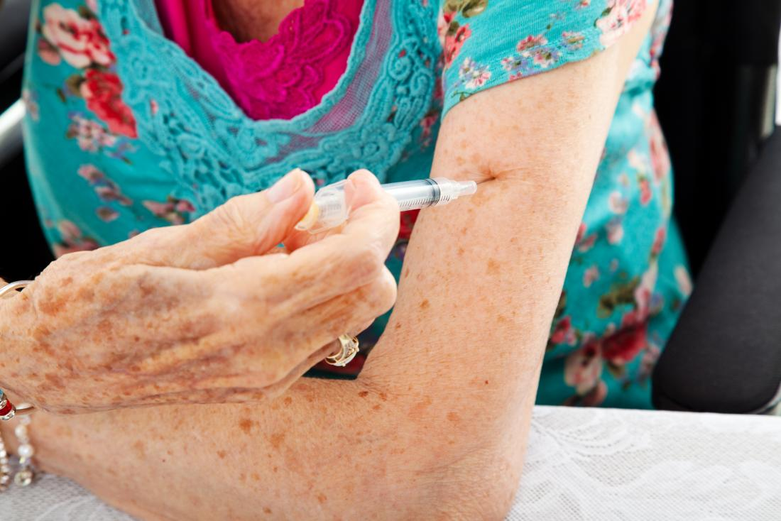 Senior woman using Enbrel or Humira injection to treat rheumatoid arthritis