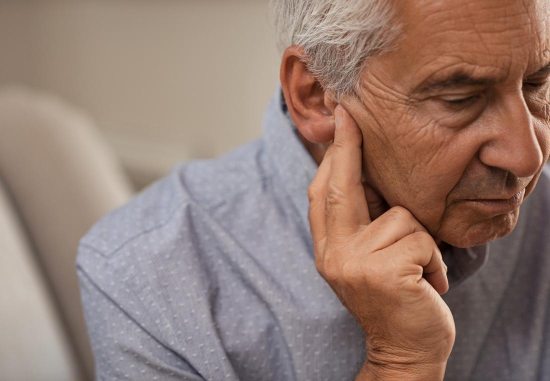 Senior man touching ears because of hearing loss