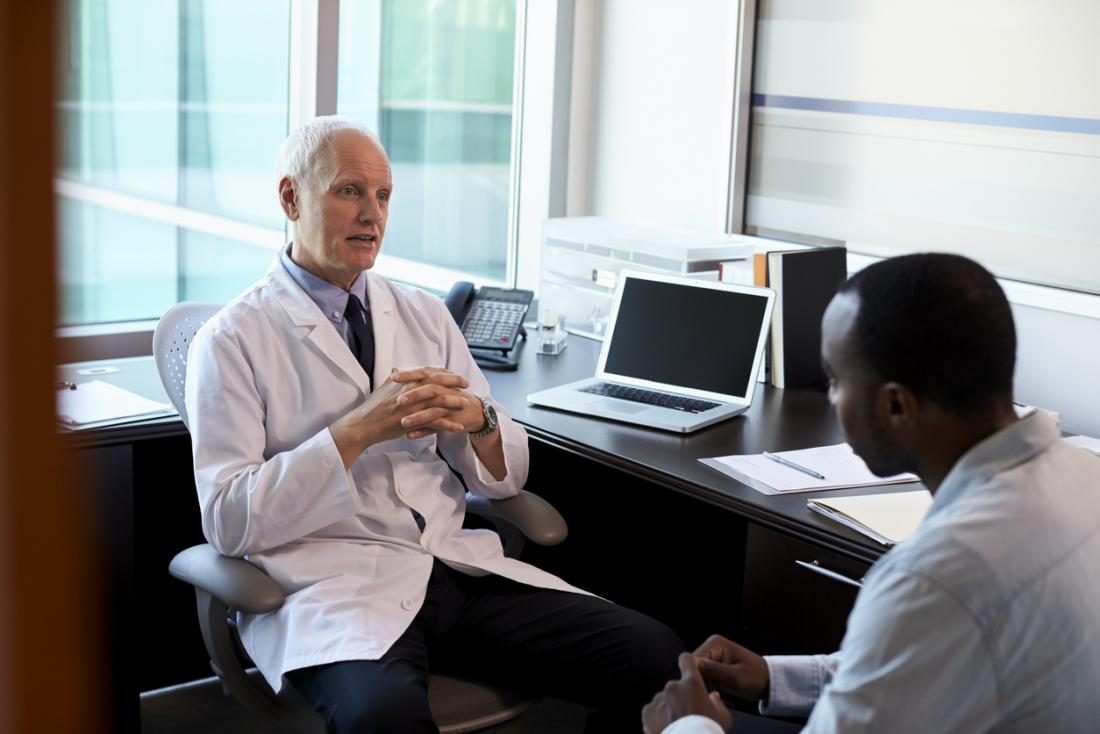 Senior white male doctor with young black male patient, in discussion.