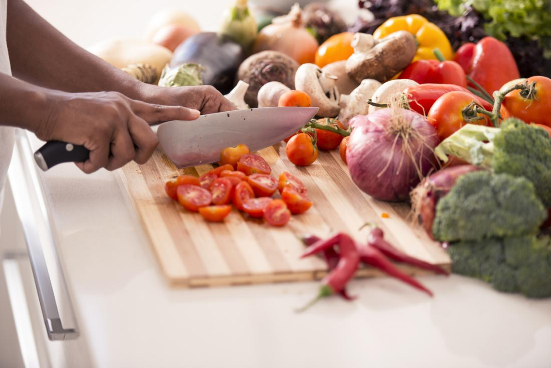 tomatoes being chopped up surrounded by other healthy vegetables