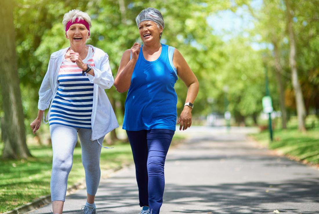 two middle aged women fitness walking through park