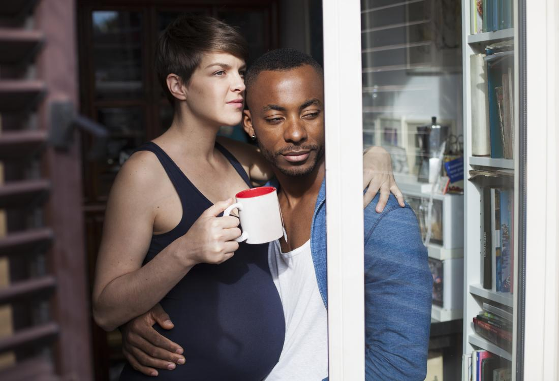 Pregnant woman embracing her partner