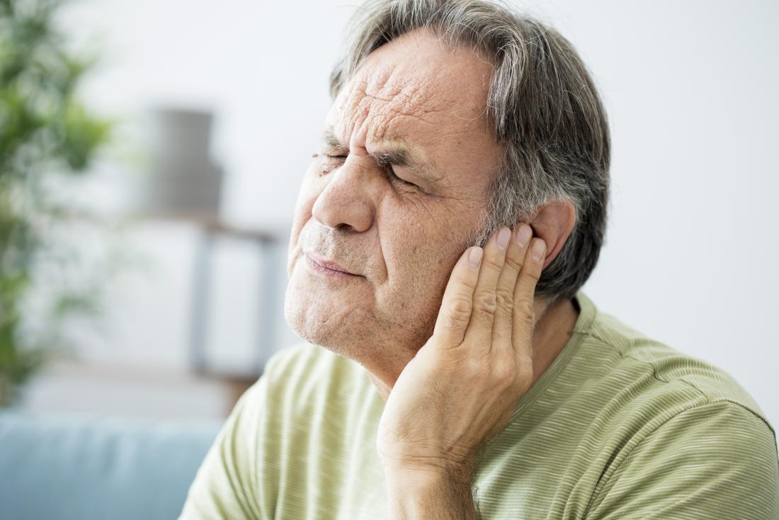 Older man with left ear pain alongside tonsil stones.