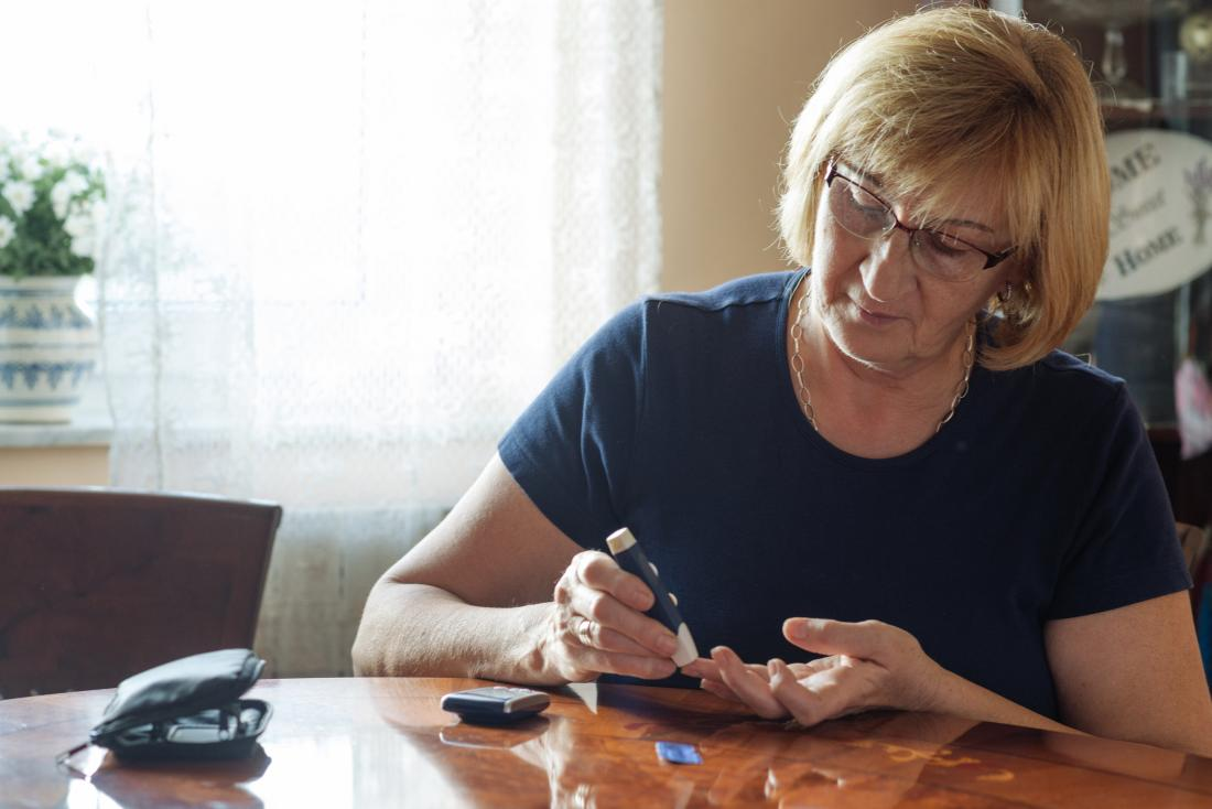senior woman measuring her blood sugar