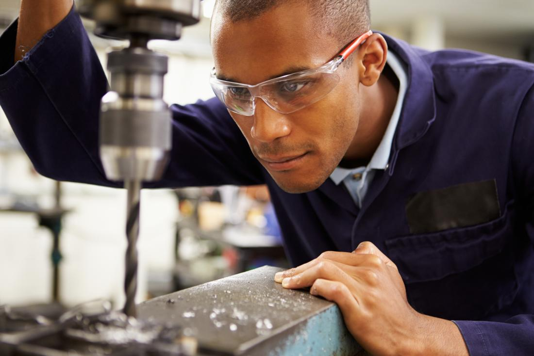 young man wearing protective eye glasses at work