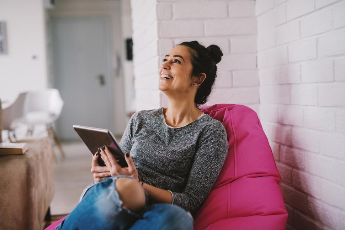 HAppy woman smiling and laughing sitting on beanbag