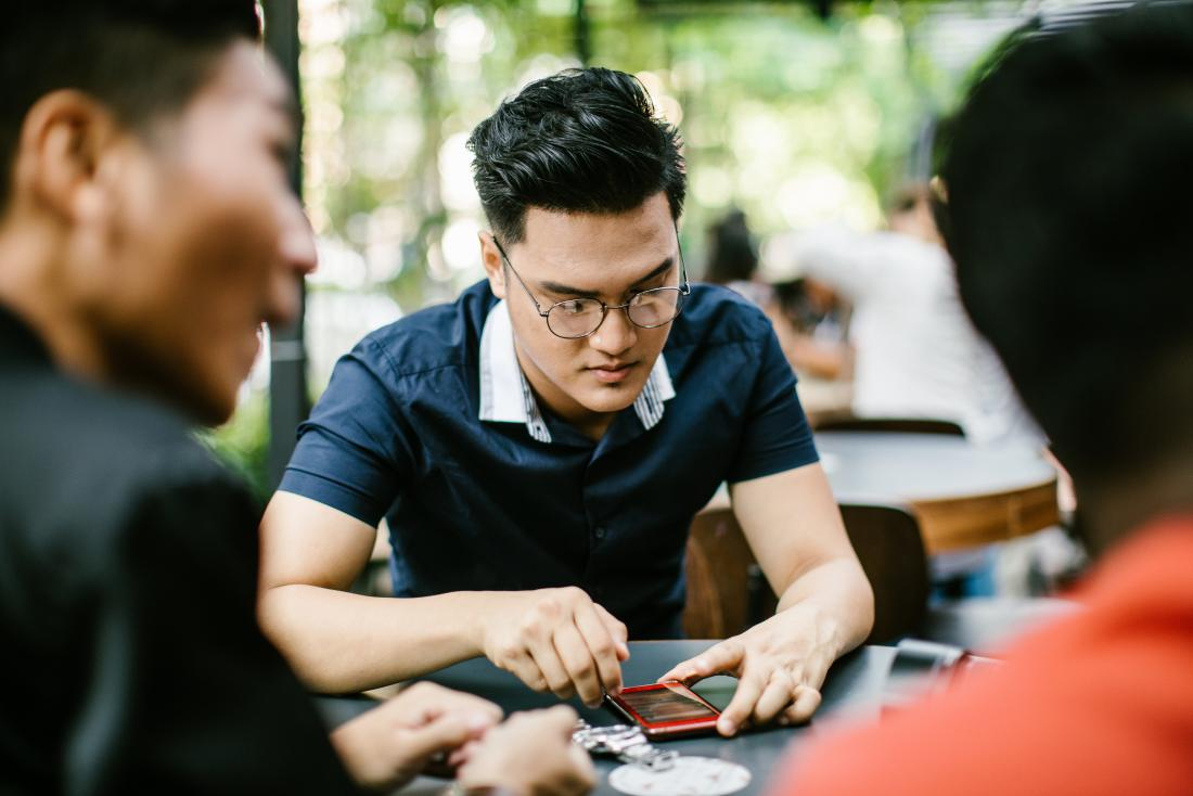 Distracted man with bipolar and adhd playing with smartphone and outdoor cafe with friends