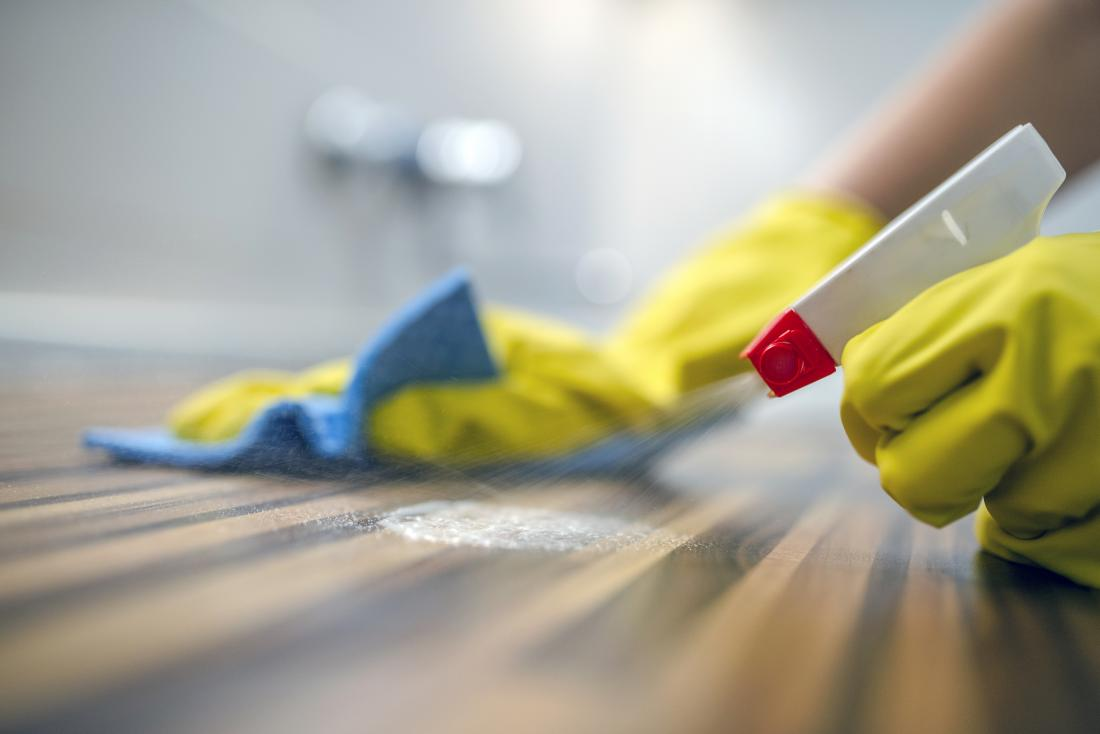 Person using cleaning products while wearing protective gloves