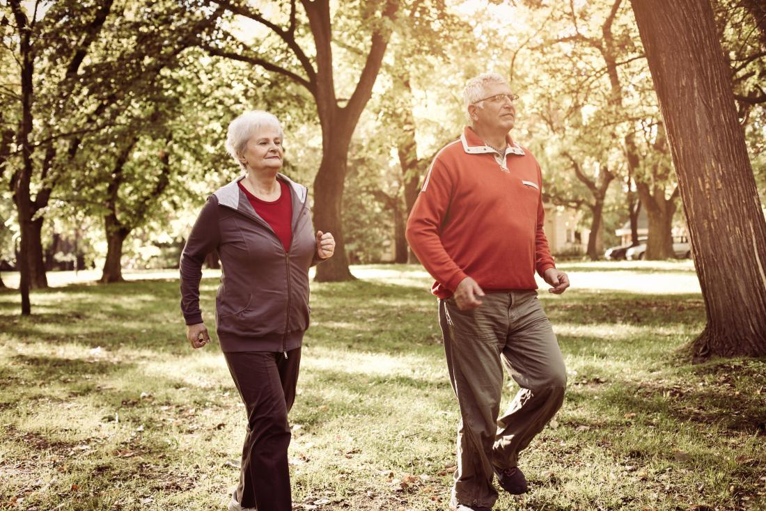 Senior couple walking or jogging for exercise in park