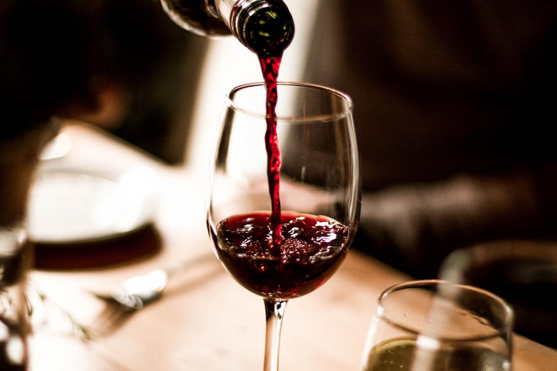 Wine being poured into glass combining alcohol with ibuprofen
