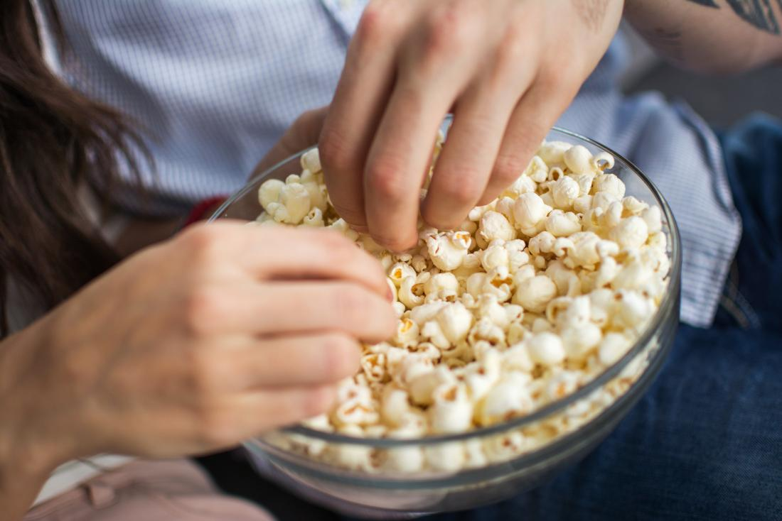 close up of hand in bowl of popcorn