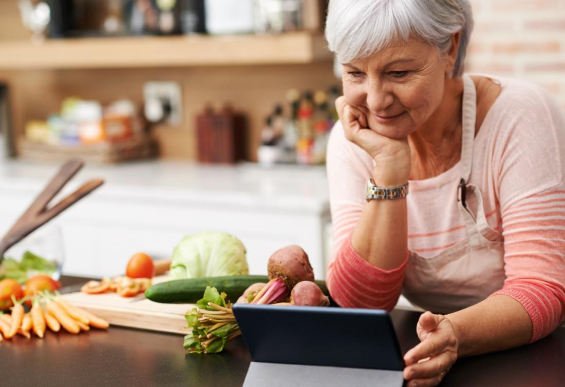 senior looking at a tablet while surrounded by vegetables