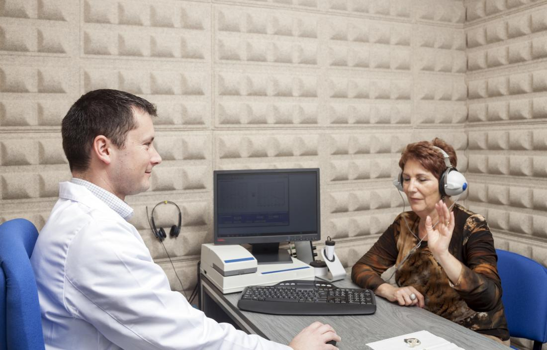 older woman donning headphones for a test in the lab