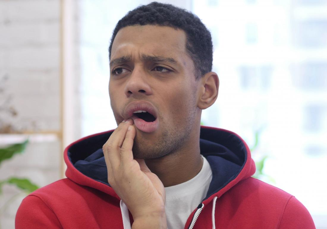 man holding mouth in pain due to mouth sores