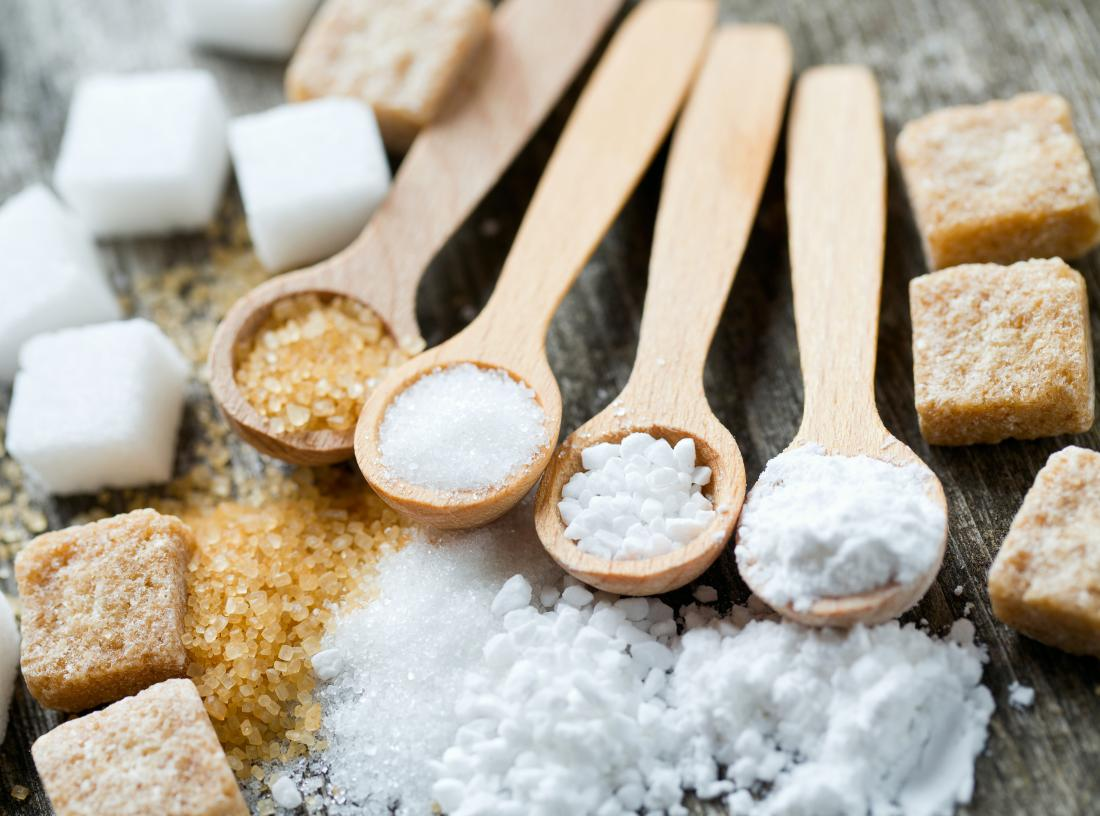 Brown, icing, granular and white sugar on wooden spoons and in cubes
