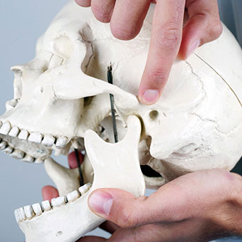 TMJ syndrome can manifest as pain and swelling in the jaw joint and surrounding facial muscles.