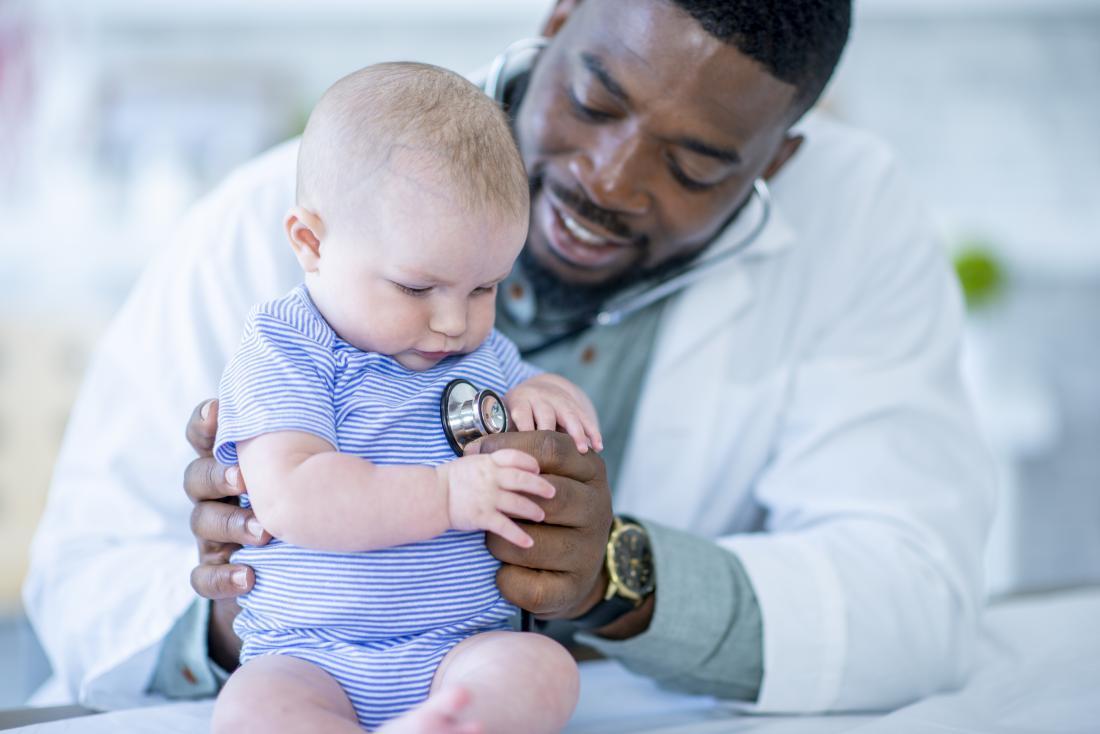 Doctor using stethoscope on baby