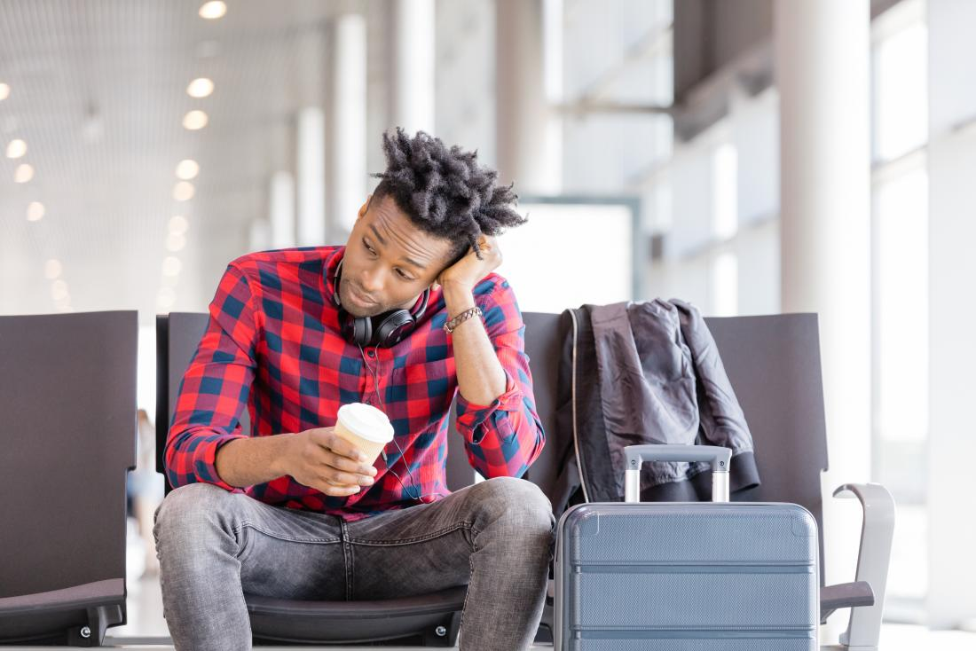 Man in airport going without sleep holding takeaway coffee looking tired
