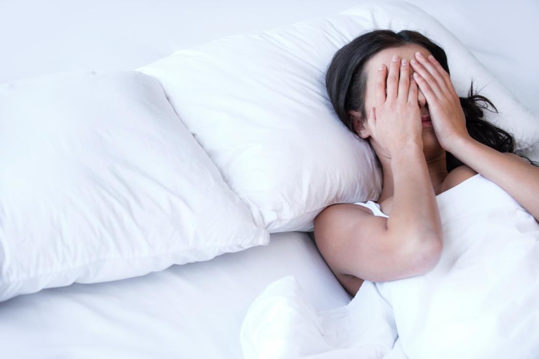 Woman in bed going without sleep suffering from insomnia covering eyes with hands