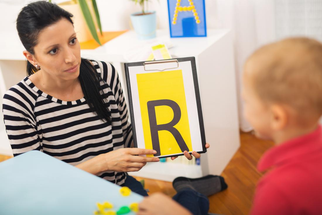 Speech therapist talking to young boy with a speech disorder