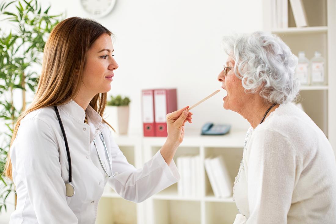 Doctor examining a senior patients throat