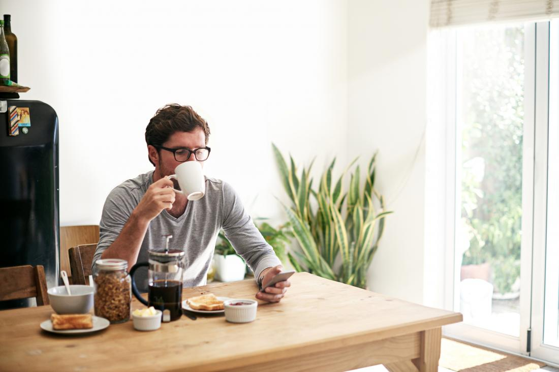 Man sitting at table eating breakfast and drinking coffee