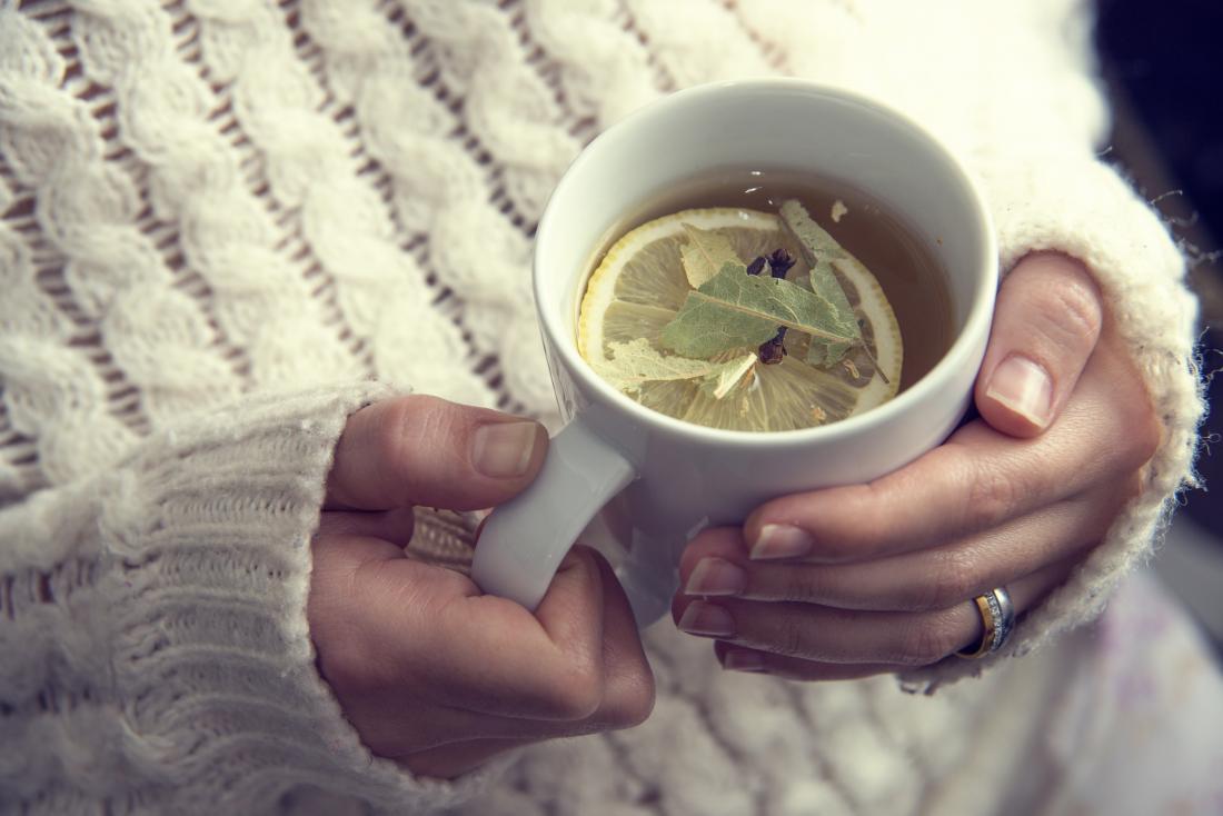 Person holding mug of herbal tea