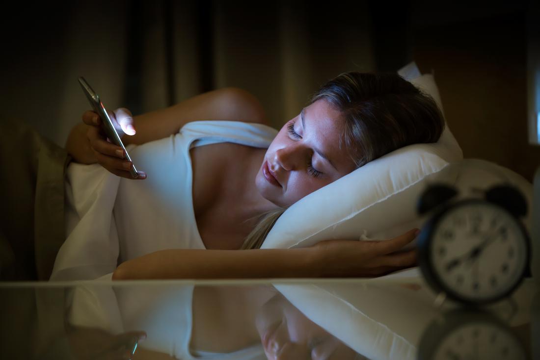 Woman awake in bed at night because of bipolar mania symptoms