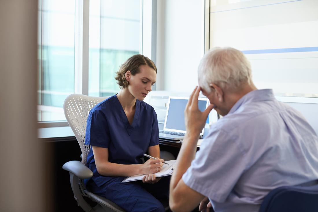 gp listening to depressed senior male patient and taking notes