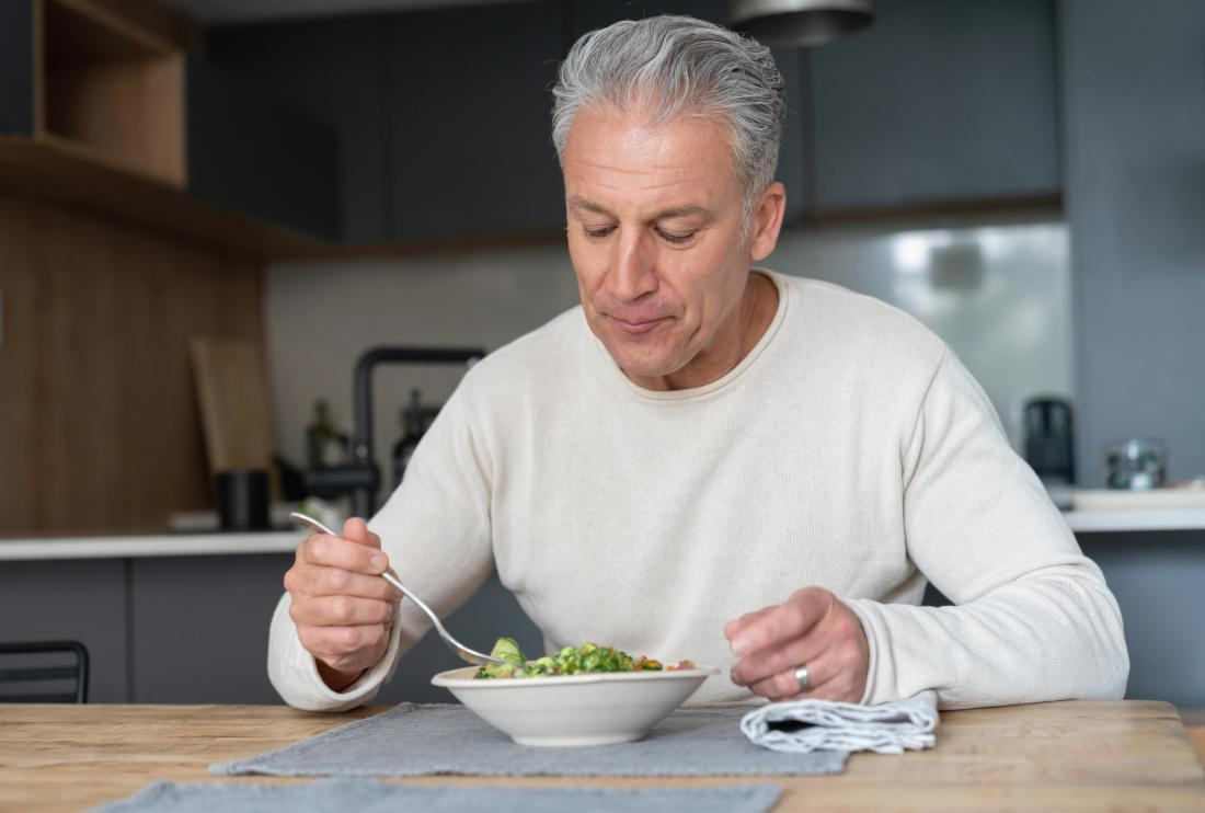 Older man with appetite loss due to bipolar disorder sits alone at table eating a salad.