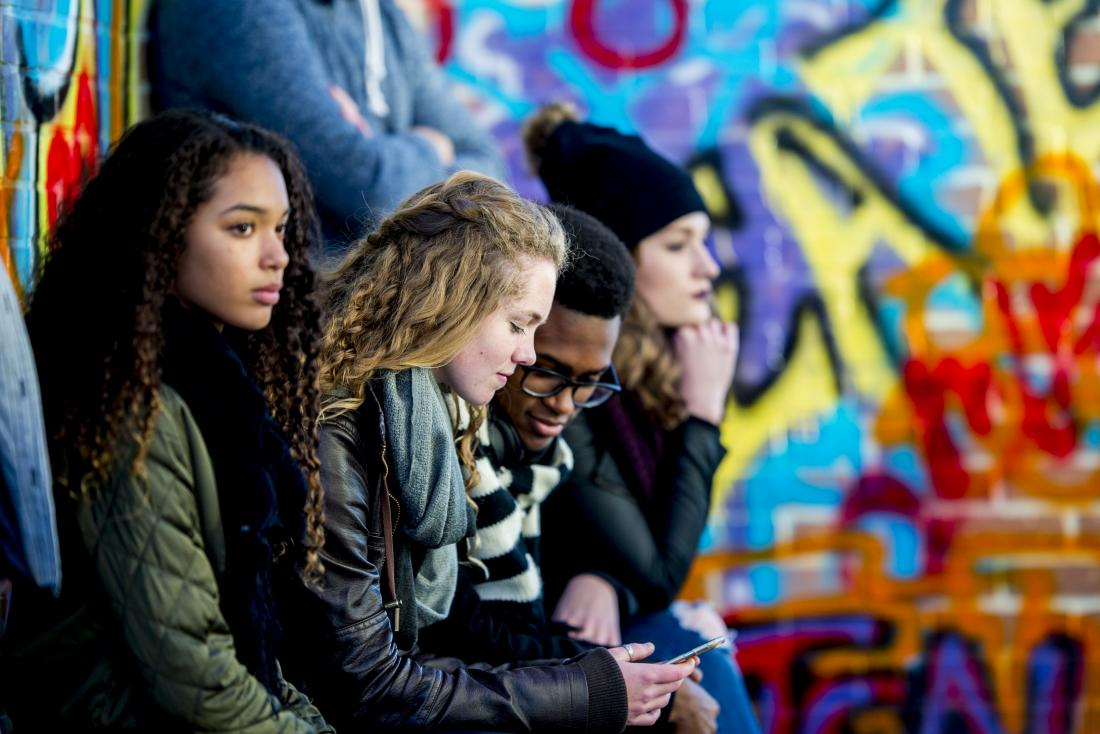 Group of teenagers sit in a row in front of a wall of graffiti.