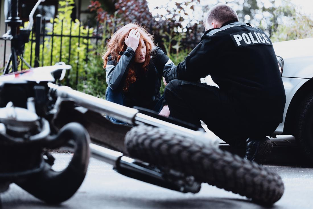 woman speaking to policeman after motorbike accident