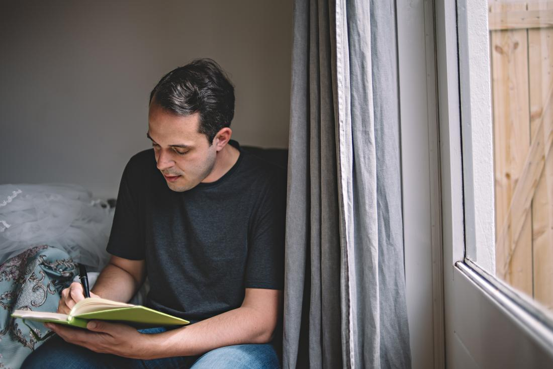 Man writing journal or diary next to window