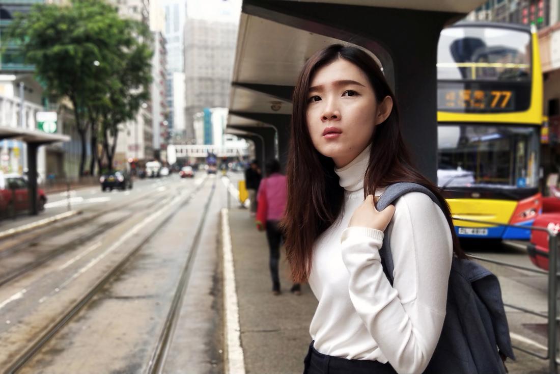 Asian woman walking across busy city street or road