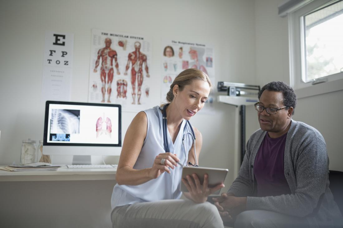 Doctor showing patient the appearance of herpes with pictures on tablet device