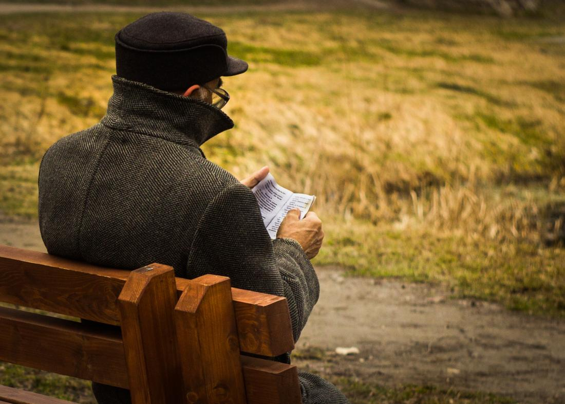 older man sitting on bench reading a book