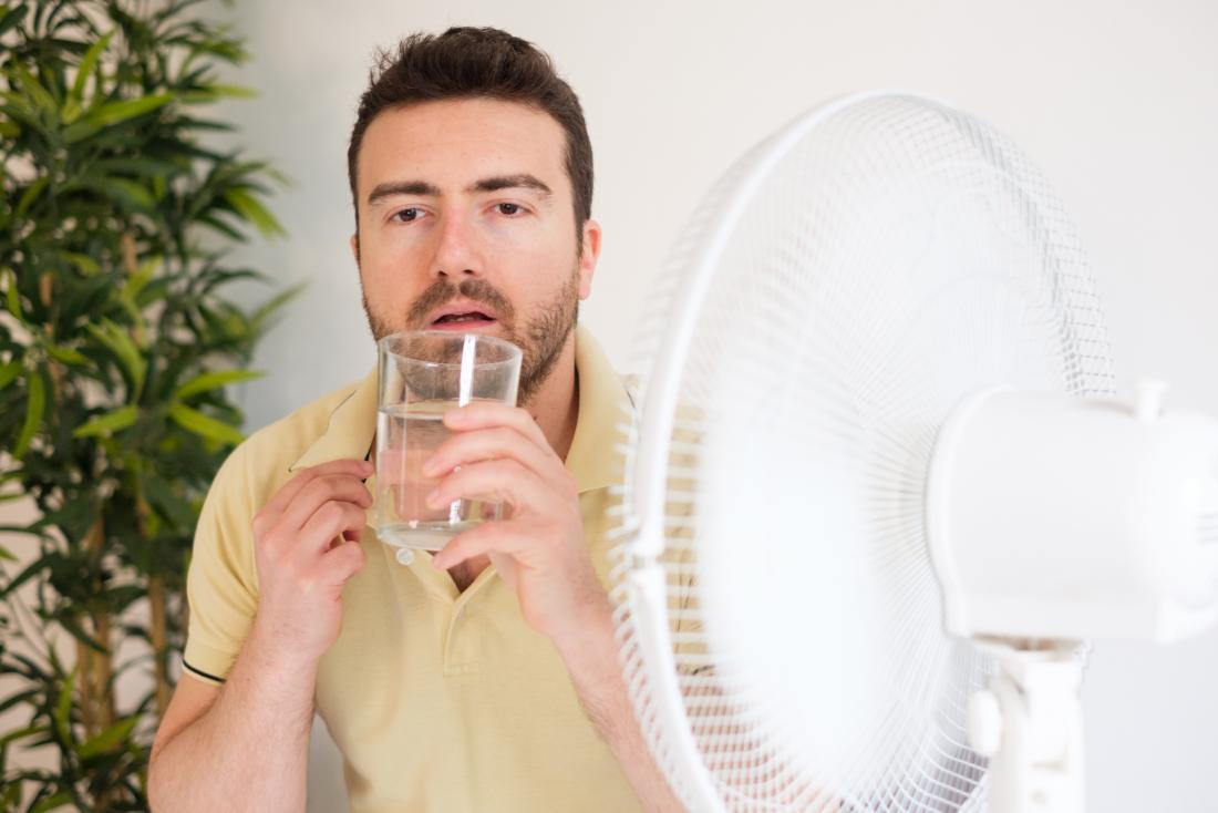 man drinking glass of water in front of electric fan