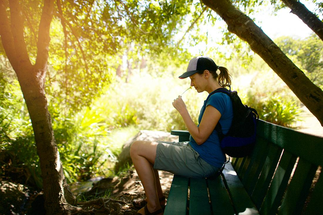 female hiker sitting on a bench in the shade sniffing a flower