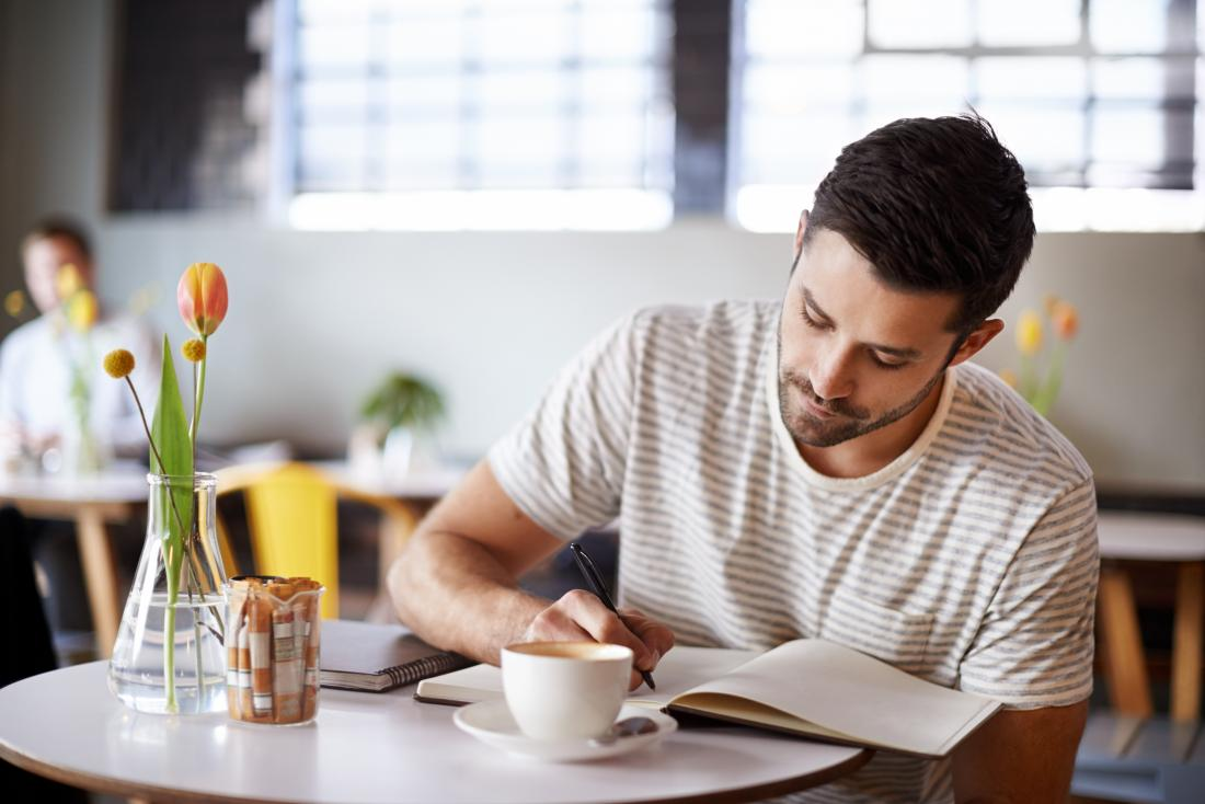 Man writes in a journal in a cafe to keep track of psoriasis and psoriatic arthritis triggers