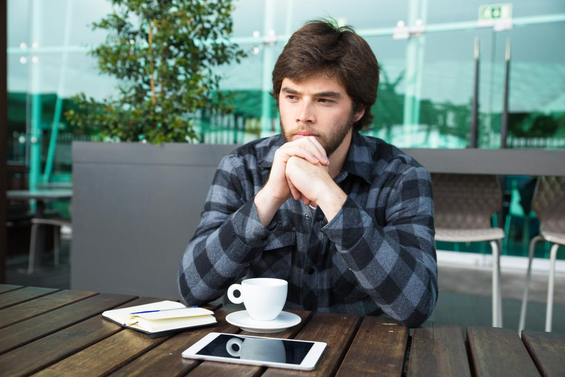 man sitting having coffee alone due to psoriatic arthritis and depression