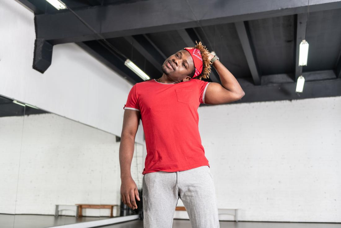 Man stretching neck in gym preparing for exercise.