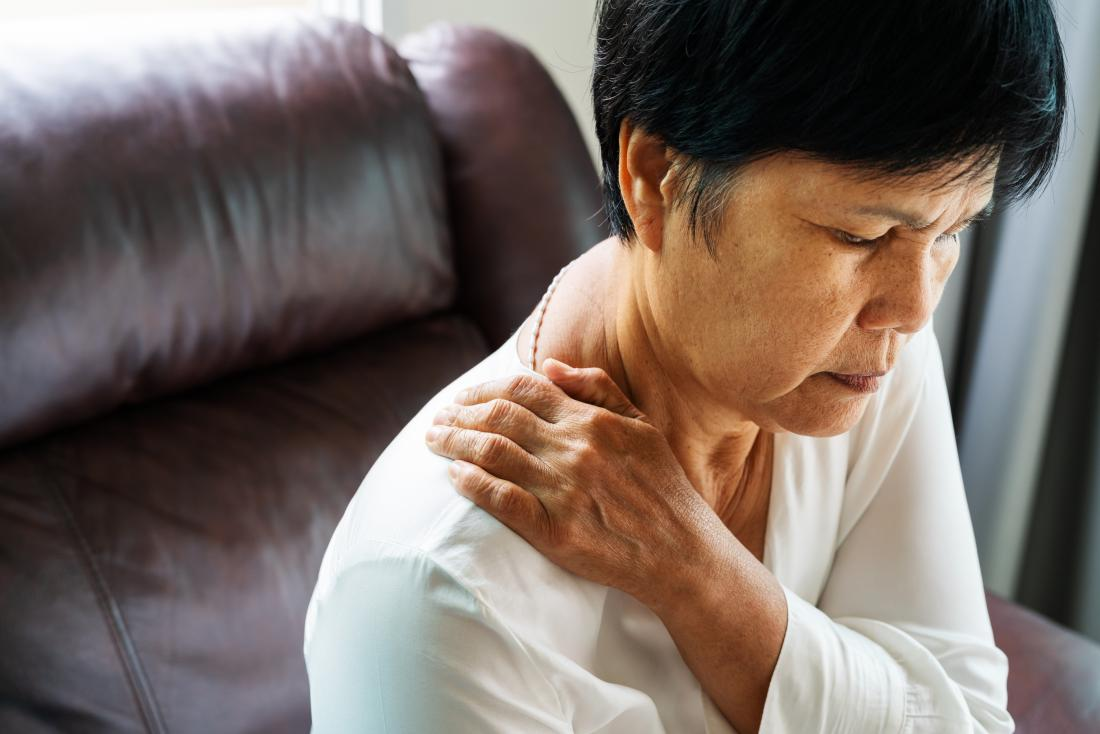 Woman with Bulging disc in the neck holding neck and shoulder in pain
