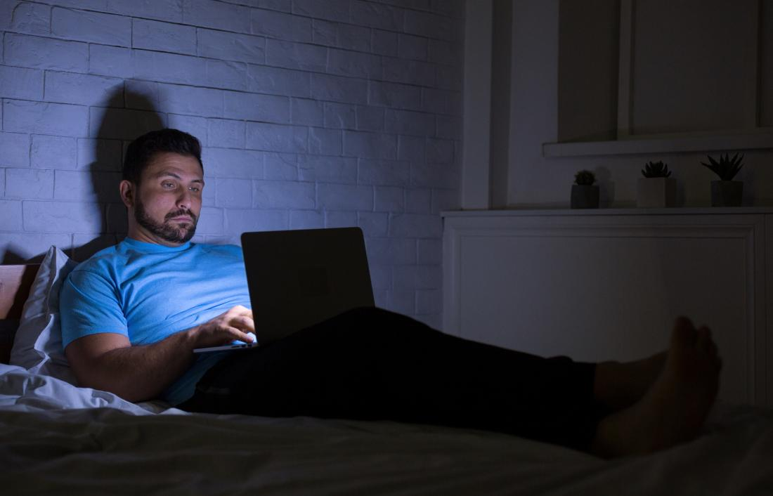 Man staying up late at night on laptop with bright screen