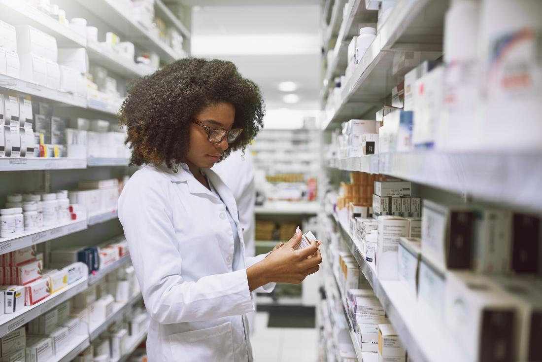 pharmacist looking at prescription medication in pharmacy